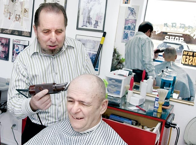 The Daily Courier/Les Stukenberg<br> Steve Woodham, owner of the Haircut King, trims up his brother-in-law Mike Baldassin's hair at the shop.