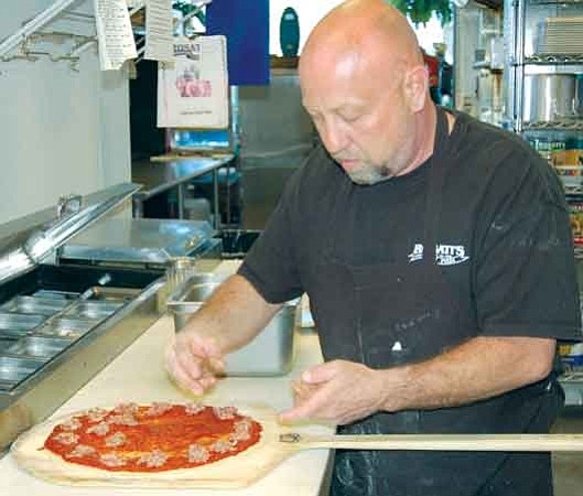 The Daily Courier/Jason Soifer Ron Thomson, Don Stedman's employee, makes a sausage pizza at Rosati's Pizza Thursday afternoon.