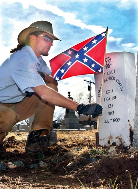 "The Daily Courier/Les Stukenberg <br> Yavapai County Facilities employee Jeff Banus places a Confederate flag in front of the new headstone for ""Chloride Jack"" Owens at the Citizens Cemetery in Prescott."
