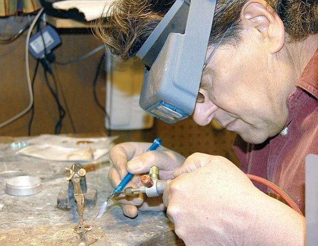 The Daily Courier/Jason Soifer<br> Fred Tenca does some soldering at his desk in the Kikkapoo Express Indian Jewelry store on Whiskey Row.