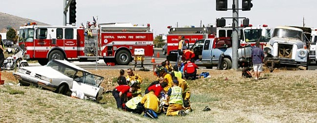 The Daily Courier/Les Stukenberg<br> Emergency personnel treat two people who received injuries in the two-vehicle collision at the intersection of Highway 69 and Navajo Drive in Prescott Valley Monday morning.