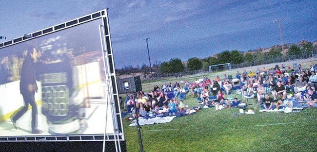"The Daily Courier/Nathaniel Kastelic<br> People lounge on the lawn of Heritage Park softball field to enjoy Arizona Mobile Cinema's feature presentation of ""Night at the Museum"" this past summer in Prescott."