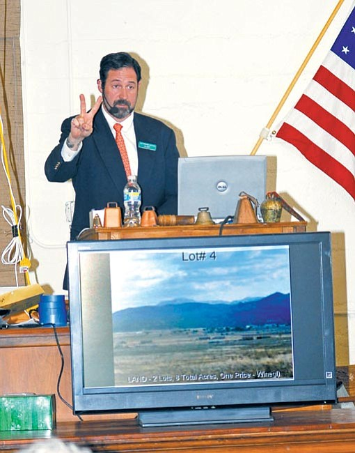 The Daily Courier/Jo. L. Keener<br> Kirk Vogel, auctioneer for Batterman's Auction & Gallery, uses a television to show bidders a property for sale during an auction Saturday.