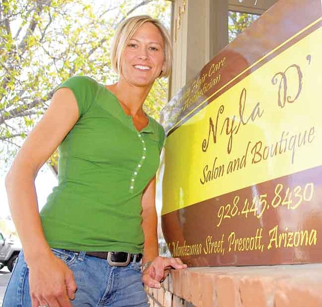 The Daily Courier/Matt Hinshaw Jenny Bacon, owner of Nyla D' Salon and Boutique, stands next to her downtown Prescott Business Monday afternoon.