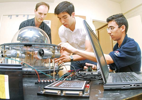 The Daily Courier/Matt Hinshaw Cory Ravetto, left, Eduardo Moreno, and René Valenzuela, members of the ERAU underwater robotic team, work on their underwater robot Monday morning inside their workshop at Embry-Riddle Aeronautical University in Prescott. The ERAU robotic team is preparing to head to a national competition in Chandler, Ariz., to demonstrate the abilities of their robot.