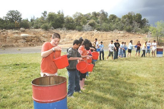 Courtesy<p> Students perform the bucket brigade during Mile High and Granite Mountain Middle Schools' participation in the Fire Trap program.