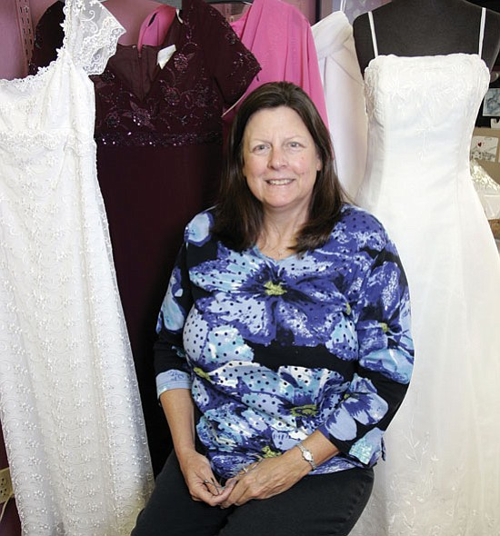 The Daily Courier/Les Stukenberg<p> Rebecca Spiller, owner of Formally Yours in Prescott, poses amongst some of the many bridal and cocktail dresses she has in her shop.