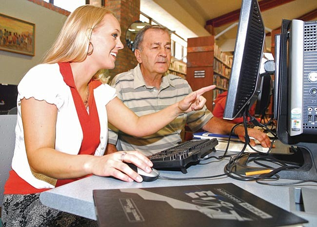 The Daily Courier/Matt Hinshaw<p> Angela Ingrau, Chino Valley Class of 1998, shows Andy Viliborghi, Prescott High School Class of 1958, how she uses the Internet to track down fellow classmates to notify them of upcoming reunions Friday afternoon at the Prescott Public Library.