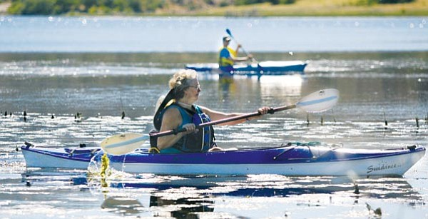 The Daily Courier/Les Stukenberg<br> Katie Baird and her son Dylan paddle through the shallows on Watson Lake in their kayaks on Wednesday.