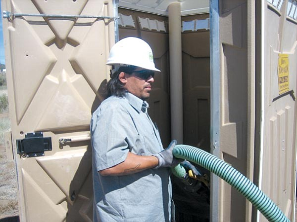 The Daily Courier/Ken Hedler<br> Richard Daniels, a driver for Julio's Honeywagon Inc. of Chino Valley, pumps waste from a portable toilet unit Friday morning at a construction site in Dewey-Humboldt.