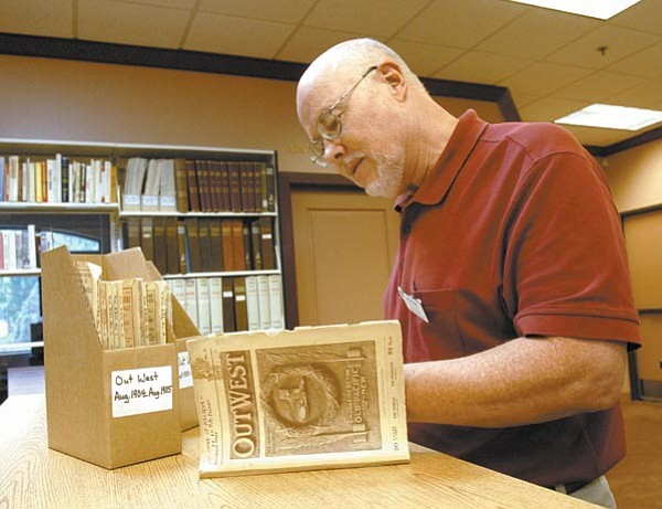 The Daily Courier/Jo.L. Keener<br>  Tom Collins, who works as an archivist at Sharlot Hall Museum, compares information in old paperback magazines Saturday at the museum's new Prescott archive building.