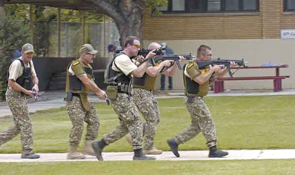 "The Daily Courier/Jo.L.Keener<br> Yavapai County Sheriff's officers move through the quad during a drill at Mile High Middle School Wednesday afternoon as they search for an ""active shooter."""