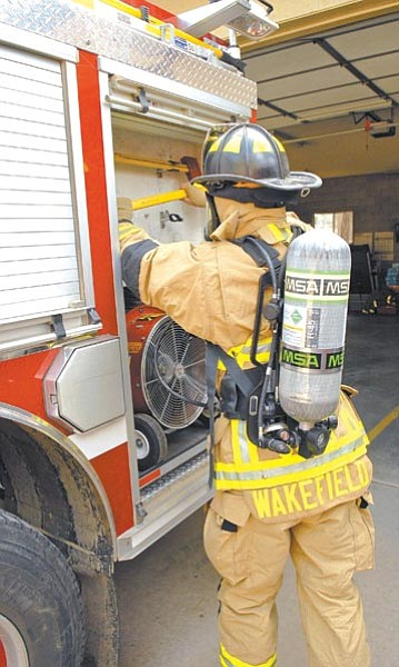 Jo. L. Keener/The Daily Courier<br> Groom Creek firefighter Luke Wakefield gets equipment from a truck while wearing a new self-contained breathing apparatus the department purchased with grant money.