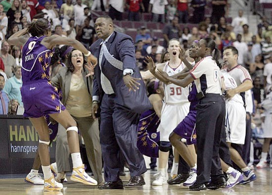 Jerry S. Mendoza/<br>The Associated Press<br>Detroit Shock assistant coach Rick Mahorn, center, pushes Los Angeles Sparks' Lisa Leslie to the ground during a melee in the closing seconds of their WNBA game on July 22 in Auburn Hills, Mich. Mahorn, who was ejected, was attempting to keep Leslie from approaching the Shock bench during a bench-clearing fight in which four were ejected.