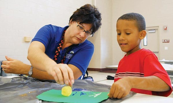 Matt Hinshaw/The Daily Courier<p> Assistant to the Director of Kids and Company Joann Mattson works with Kai Hawkins, 6, at Taylor Hicks Elementary School during the Kids and Company After School Program in Prescott.