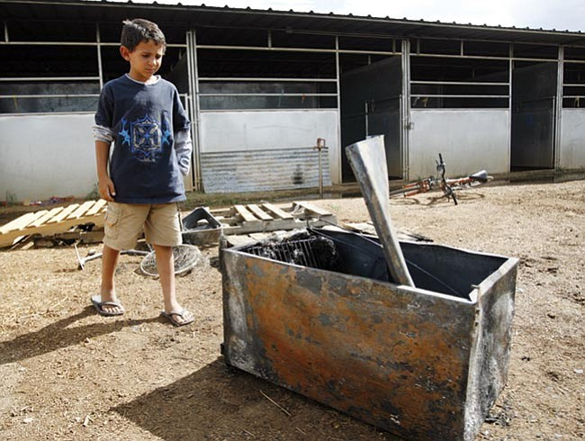 Les Stukenberg/The Daily Courier Eight-year-old Bailey Thibeault looks at the small refrigerator that apparently caused a fire in a stall of a barn at Yavapai Downs on Tuesday night. Thibeault, who was on scene when the fire was being put out, said the scariest part for him was when a running horse tried to stop and flipped over a gate.  He added that he thought the horse was OK.