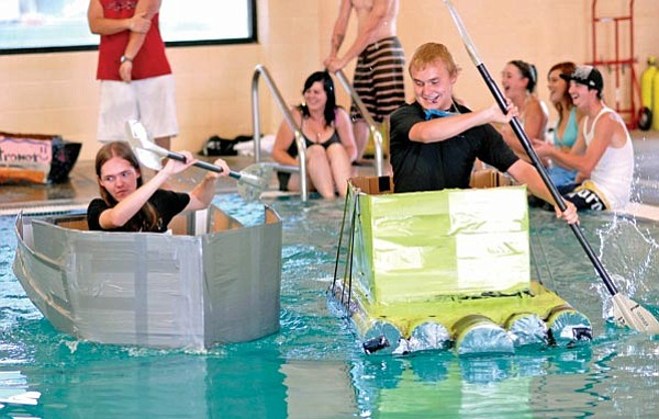 Jo. L. Keener/The Daily Courier<br> Luke Thurman, left and Ian Isley paddle their cardboard boats Thursday in the YMCA pool. The Kestrel art students made the boats entirely from cardboard and duct tape as part of an art project.