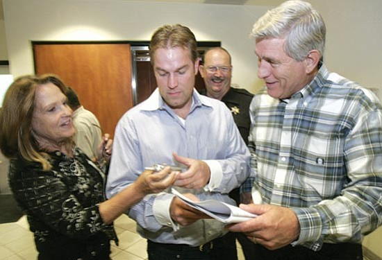 Les Stukenberg/The Daily Courier<p> Barbara Waugh hands a cell phone to son Kyle as her husband Sheriff Steve Waugh reads the initial vote updates that show the incumbent well ahead of challenger Ernie Cox.