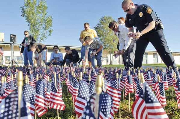 Jo. L. Keener/The Daily Courier<br> Prescott High students and Police place small American flags at Prescott High School Thursday morning in remembrance of those who died in the September 11 attacks on America. 2977 flags were placed at the school during the memorial ceremony.
