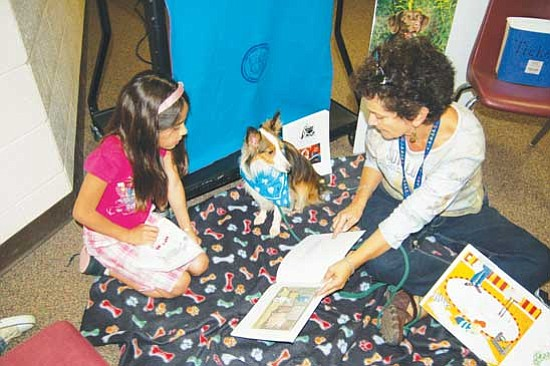 Jerry J. Herrmann/ The Daily Courier<p> Minelly Alcala, a  second-grader at Mountain View Elementary School, reads out loud to Wrigley, a reading education assistance dog, as Joanne Hayden, MVES special education teacher, holds the book.