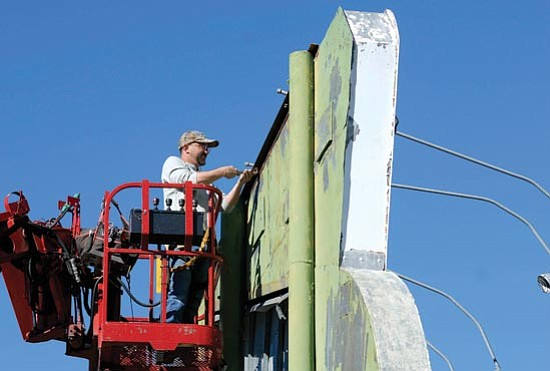 Jo. L. Keener/The Daily Courier<p> Mark Goudil of A & B Sign Company works to remove lights from the old Senator Drive-In sign Wednesday morning.