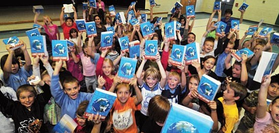 Les Stukenberg/The Daily Courier Third grade students at Coyote Elementary School in Prescott Valley hold up their new dictionary's they received from the Bradshaw Kiwanis Club on Wednesday. All 103 third grade students at the school and over 400 in the Humboldt Unified School District received the dictionaries courtesy of the club.