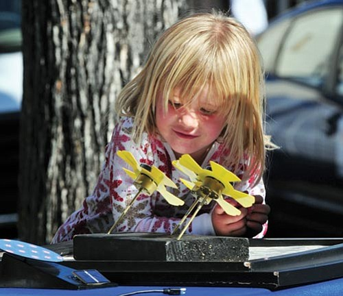 Les Stukenberg/The Daily Courier<p> Daisy Carothers studies one of the displays in the Kids Zone at the Solar Energy Exhibit Saturday on the Courthouse Plaza in downtown Prescott.