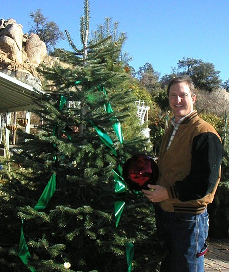 Courtesy Ken Lain poses with a living Christmas tree.