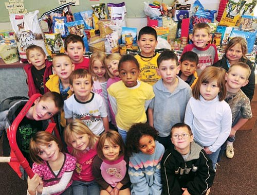 Les Stukenberg/The Daily Courier<br> Students in Melissa Walker's first grade class at Humboldt Elementary School gather Thursday with the over 500 pounds of dry dog food, 50 cans of dog and cat food and $250 in cash that the school raised for United Animal Friends and Prescott Animal Lifesavers.