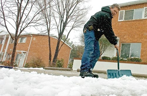 Matt Hinshaw/The Daily Courier<p> Frank Hargett, a maintenance worker for an apartment complex on Thumb Butte Road, shovels snow out of the parking area Tuesday afternoon in Prescott.