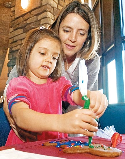 Matt Hinshaw/The Daily Courier<p> Kristin Joseph helps her daughter, Emery, 4, decorate a gingerbread man with colored icing Saturday afternoon at the Prescott Resort.