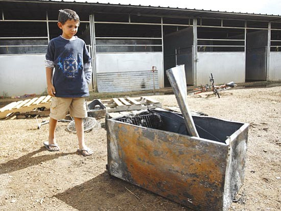 Les Stukenberg/<br>The Daily Courier<br>In this Aug. 13, 2008, file photo, 8-year-old Bailey Thibeault checks out the small refrigerator that apparently caused a fire in a stall of a barn at Yavapai Downs in Prescott Valley. Thibeault who was on scene when the fire was being put out said the scariest part for him was when a running horse tried to stop and flipped over a gate.
