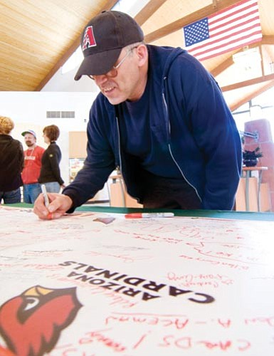 Les Stukenberg/The Daily Courier<p> Carl Sawyer of Humboldt signs the Super Bowl support poster for the Arizona Cardinals that made its way from Prescott Valley, then to Prescott and onto Chino Valley on Saturday.