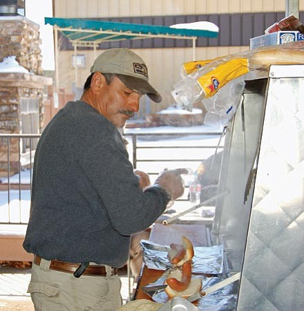 Paula Rhoden/The Daily Courier<p> Hot dog vendor Pat Gregory was back to work Friday under his familiar canopy