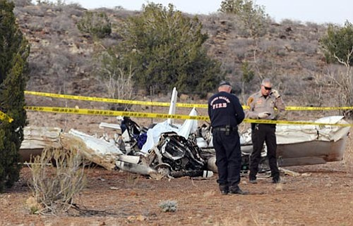 Les Stukenberg/The Daily Courier<p> Yavapai County Sheriff's Sgt. Mark Howard looks at the ID of the victim of a fatal plane crash near Sweet Valley Farm in Paulden on Wednesday evening. Chino Valley Fire Department Engine 63 was the first unit on scene and reported that witnesses said the plane spiraled into the ground.