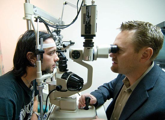 Les Stukenberg/The Daily Courier<p> Kris Espinosa, at left, gets his right eye examined by Dr. Scott Markham after he had cataract surgery on Monday that was paid for by the Lions Club Foundation.