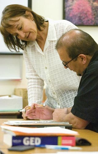 Matt Hinshaw/The Daily Courier<p> Cheryl Casey, GED class instructor and coordinator, works with a student on percentages Tuesday morning at Yavapai College in Prescott.