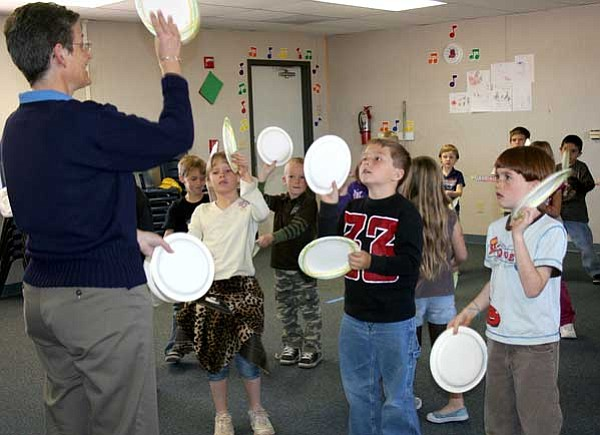 Sue Tone/Prescott Valley Tribune<br> Using paper plates as percussion instruments, Amy Van Winkle leads Coyote Springs Elementary School first-graders in a rhythm and movement activity.