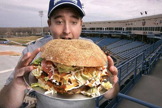 Rex Larsen/<br>The Grand Rapids Press, AP<br>Josh Kowalczyk, an intern with the West Michigan Whitecaps, in Comstock Park, Mich., poses with the team's $20 burger which features a sesame-seed bun made from a pound of dough, five 1/3-pound beef patties, five slices of cheese, nearly a cup of chili and liberal doses of salsa and corn chips.