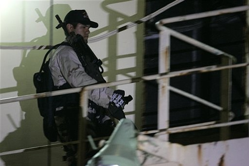 An unidentified armed man is seen on deck of the American ship, the Maersk Alabama, whose captain remains held hostage by Somali pirates, as it arrives in Mombasa, Kenya, guarded by Navy Seals and with the 19 remaining crew members aboard, Saturday April 11 2009. Capt. Richard Phillips is still being held in the lifeboat hundreds of miles from land. U.S. warships are nearby monitoring the situation. The U.S.-flagged ship was attacked by Somali pirates firing automatic weapons Wednesday but its unarmed crew locked themselves in a secure room and then overpowered one of the pirates. (AP Photo / Karel Prinsloo)
