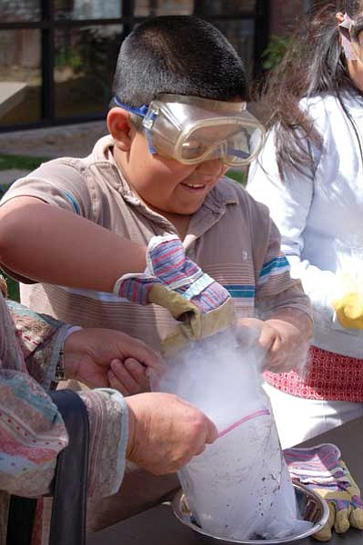 "Joanna Dodder, file/The Daily Courier<br> Dry-ice fog rises from a bag as Jonathan Gonzalez creates a comet during last year's Spotlight on the Stars event at the Prescott Public Library. ""Astro-guy"" Ed Anderson returns this Saturday to help more children make comets."