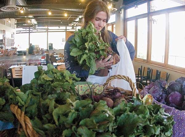 Matt Hinshaw/The Daily Courier<br> Cori Keene, a sophomore in Agro Ecology, picks up a bundle of beets during the Community Supported Agriculture program's food distribution at Prescott College.