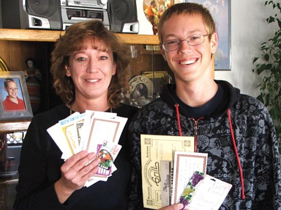 Sharon Hendricks and her son Alex of Prescott Valley display grand prize gift certificates they won in United Animal Friends' Best Restaurants Raffle.