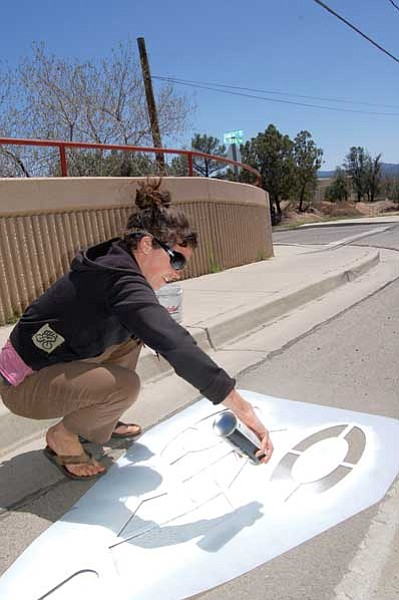 Cindy Barks/The Daily Courier<br> Local bicyclist Carin LeFevre applies spray paint to one of the bike symbols in the bike lane along Willow Creek Road on Sunday. LeFevre and other cyclists volunteered to freshen up the dozens of bike symbols that border Willow Creek, Prescott Lakes Parkway, and Smoketree Lane.