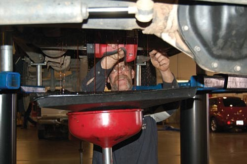 Jason Soifer/The Daily Courier<br> Master Technician Rosco Hunt works on the transmission of a Dodge 3500 at the York Dodge Chrysler and Jeep dealership Friday afternoon. Despite Thursday's announcement that Chrysler filed for Chapter 11 bankruptcy, General Manager Toby York said Friday that his family's dealership is sticking around for years to come.