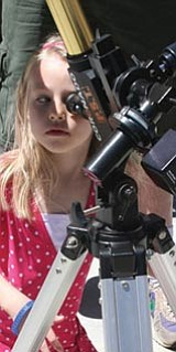 Children will have the opportunity to peek through telescopes at the fourth annual Student Astronomy Day today at Watson Lake Park. In this photo, a young girl looks at the sun safely through a solar telescope. <br>Sharon Seymour/Courtesy photo