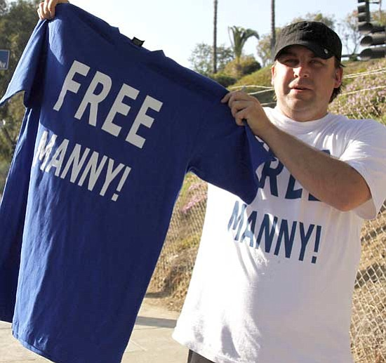 Danny Moloshok/<br>The Associated Press<br>The money trail from the steroids fallout has also reached enterprising T-shirt vendors like Kevin Rolfe in Los Angeles. Manny Ramirez will lose $7.7 million in salary, but the Dodgers stand to take a financial hit, too.