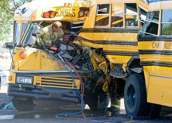 Matt Hinshaw/The Daily Courier<p> Firefighters work to cut out of the wreckage the driver of one of the school buses at the scene of a four-vehicle accident involving two Chino Valley School District buses Tuesday afternoon at the intersection of Highway 89 and Road 4 North.