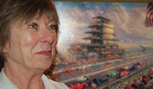 """Thomas Kinkade Gallery owner Dee Blaschke is getting out of the art business. She sold the gallery, which has been a landmark in the Prescott downtown square for the past 10 years, and today is her last day at the gallery. Blaschke sits in front of Kinkade's """"Indy Excitement.""""  Bruce Colbert/The Daily Courier"""