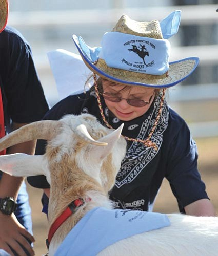 Les Stukenberg/The Daily Courier<p> Grace Woodard, 9, from Prescott gets up-close and personal with the goat named Charlie during the annual Happy Hearts Rodeo Monday.